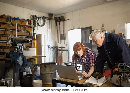 Father and daughter working on laptop in workshop - Stock Image