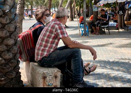 Femme portant un masque anti-pollution pendant que sa compagne fume une cigarette. - Image de l'éditeur