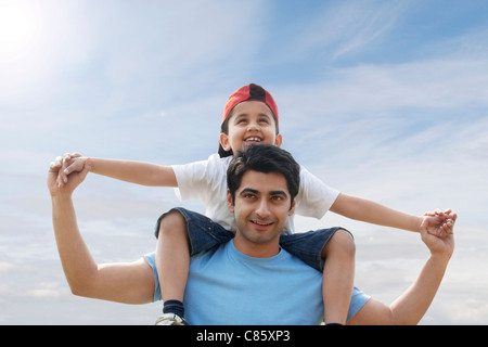 Son getting a piggyback ride from his father - Stock Image