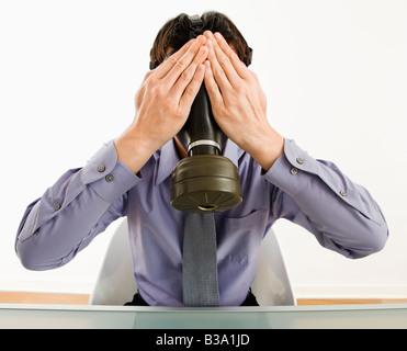 Homme d'affaires assis portant un masque à gaz tenant ses mains sur ses yeux - Image