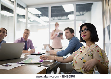 Smiling businesswoman in meeting conference room - Stock Image