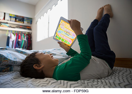 Boy feet up using digital tablet on bed - Stock Image