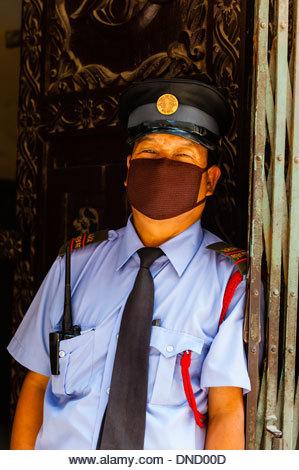Agent de sécurité portant un masque protecteur (à cause de l'air pollué), Katmandou, Népal. - Image de l'éditeur