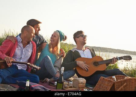 Quatre amis adultes ayant une fête sur la plage de Bournemouth, Dorset, Royaume-Uni - Image