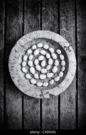 Broad bean spiral in a wooden bowl on a garden table. Monochrome - Stock Image