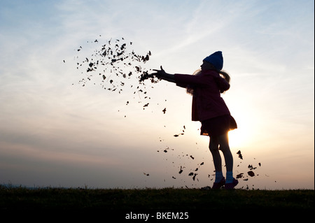 Young Girl having fun throwing leaves. Silhouette - Stock Image