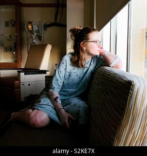 Girl in a hospital looking out window - Stock Image