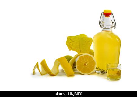 Bouteille de carafe en verre ouverte et verre à liqueur rempli de liqueur de citron jaune ou de limoncello ou de limoncino sur blanc Pelé - Image