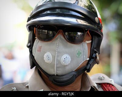 Un policier de la police royale thaïlandaise porte des lunettes de soleil en miroir et un masque protecteur à Bangkok, une ville polluée. - Image de l'éditeur
