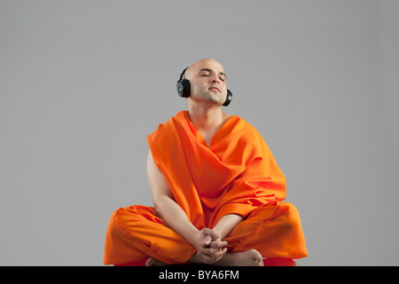 Monk listening to music - Stock Image