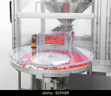 Machine Sorting Medicine Pills Before Filling - Stock Image