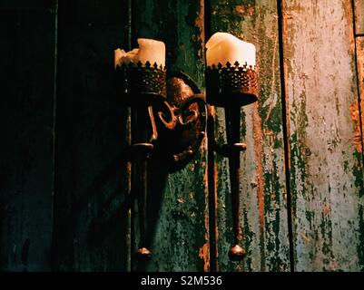 Candles in medieval torch holders against rustic green wooden wall - Stock Image