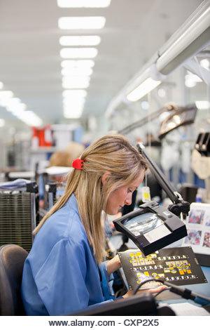 Technician examining printed circuit board in hi-tech electronics manufacturing plant - Stock Image