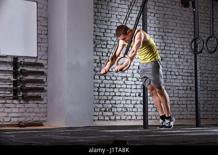 Young athletic man in the sportwear training at the cross fit gym with rings against brick wall. Sportsman in the - Stock Image