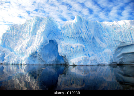 striated iceberg with blue sky and dramatic clouds - Stock Image