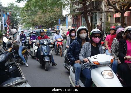 Scooters avec les coureurs, certains portant des masques, dans une rue animée à Hanoi, Vietnam - Image