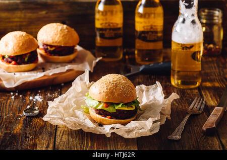 Trois hamburgers avec des bouteilles de bière blonde. - Image de l'éditeur