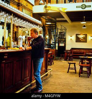Client buvant une pinte de bière au bar du pub Phoenix et Firkin, ancienne salle de billetterie du chemin de fer Denmark Hill - Image