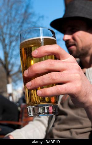 Homme buvant une pinte de bière blonde à l'extérieur du pub Uk - Image