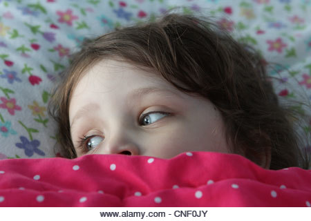 A small child in bed with blankets pulled up to eyes. - Stock Image