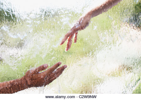 Two hands reaching out behind glass - Stock Image