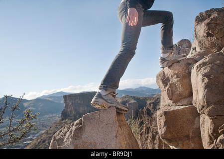woman climbs rocks - Stock Image