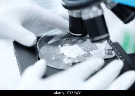 close up of hand with microscope and powder sample - Stock Image