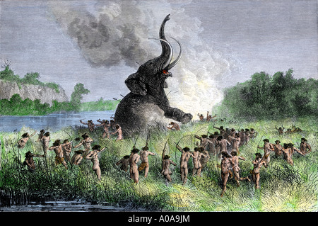 Prehistoric wooly mammoth hunters using bows and arrows. Hand-colored woodcut - Stock Image