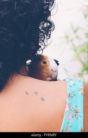 Back view of young woman with Guinea pig on her shoulder - Stock Image