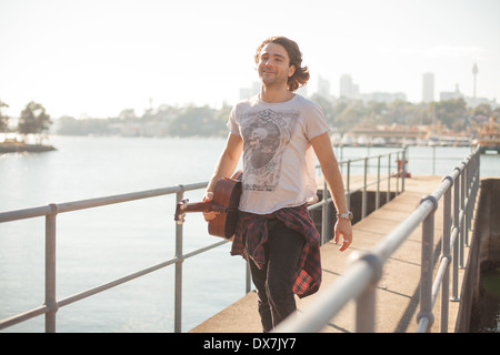 A healthy young man by the water in Sydney Harbour with his guitar - Stock Image