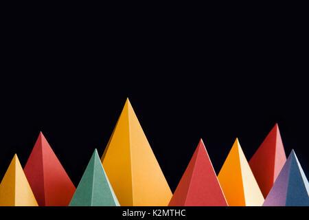 Formes géométriques abstraites colorées sur fond noir. Pyramide tridimensionnelle triangulaire. Objets de couleur malachite rose jaune bleu. Faible profondeur de champ - Image