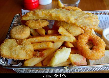 Panier de fruits de mer avec filet de poisson pané, crevettes panées, calmars avec des frites. - Image de l'éditeur