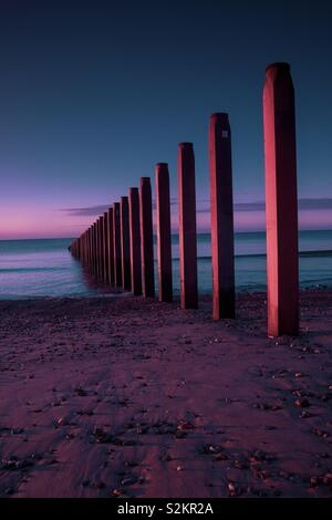 Seaside Groynes at sunrise, geometric lines, beauty in nature - Stock Image