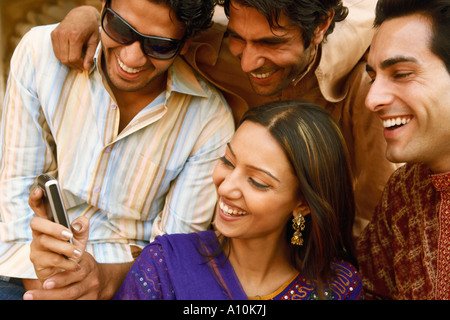 Close-up of three young men and a young woman looking at a mobile phone and smiling, Agra, Uttar Pradesh, India - Stock Image