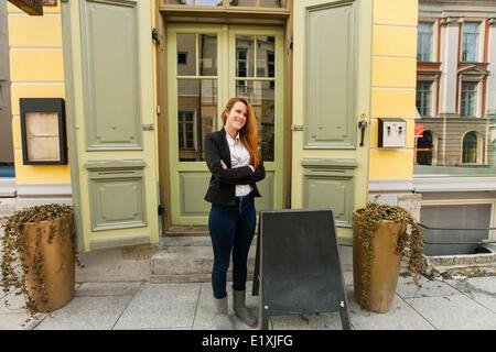 Full length of female owner standing outside restaurant - Stock Image