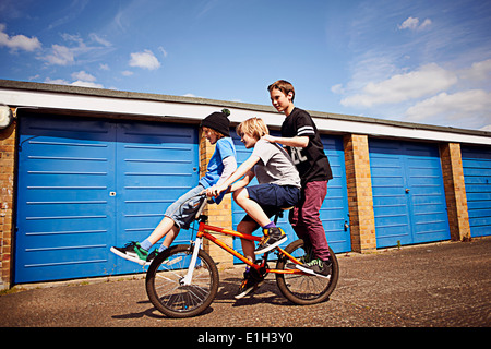 Boy giving two friends a ride on bike - Stock Image