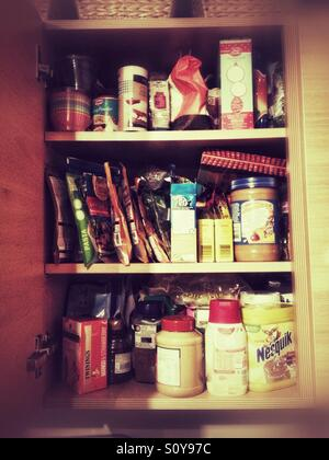 A kitchen cupboard full of food. - Stock Image