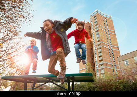 Children jumping for joy in park - Stock Image