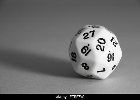 Un triacontaèdre rhombique noir et blanc meurt sur un fond gris. - image d'archive