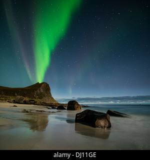 Northern Lights fill sky over Myrland beach, Flakstadoy, Lofoten Islands, Norway - Stock Image