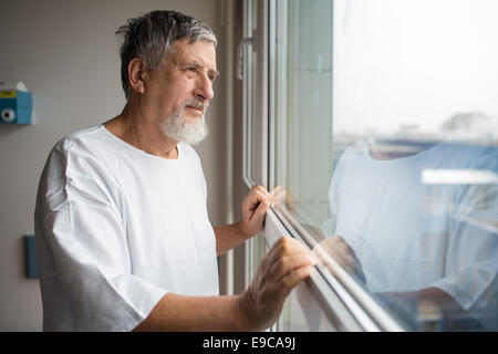 Patient at a hospital, looking from a window in his room, doing much better after the surgery - Stock Image
