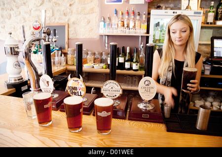 Une serveuse blonde servant des pintes de bière dans le Griffin Inn, Bath Somerset Uk - Image