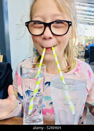 Female child drinking out of two glasses with two straws - Stock Image