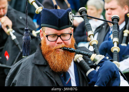 Glasgow, UK. 12th Aug, 2017. It was estimated that more than 10,000 spectators turned out to watch the final day of 'Piping Live' and the World Pipe Band Championships, an Internationally reknowned competition, take place in Glasgow Green as the finale to a week of entertainment and free concerts that have taken place around Glasgow city centre. Despite the occasional heavy rain shower, play continued and spirits weren't dampened. Credit: Findlay/Alamy Live News - Stock Image