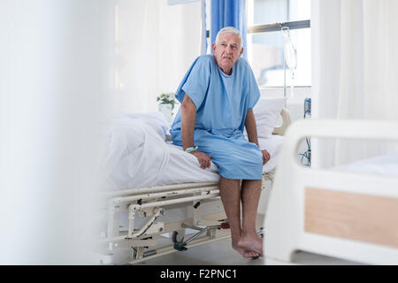 Senior patient sitting on hospital bed - Stock Image