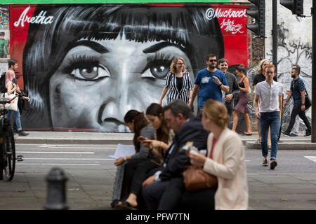 Londoners walk past a recent mural in Shoreditch (by artist Jules Muck) of Soul Queen Aretha Franklin who died a few days earlier, on 20th August 2018, in London, England. - Stock Image