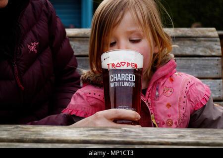 Une petite fille (3 ans), dégustation d'une pinte de bière Trooper, faite en collaboration avec le groupe britannique de heavy metal, Iron Maiden - Image