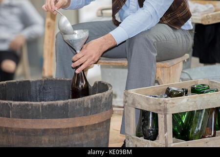 Asti, Italie - 10 septembre 2017: agriculteur met le vin en bouteilles de verre vert avec entonnoir - Image
