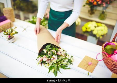 Female florist selling bouquet of amaryllises - Stock Image