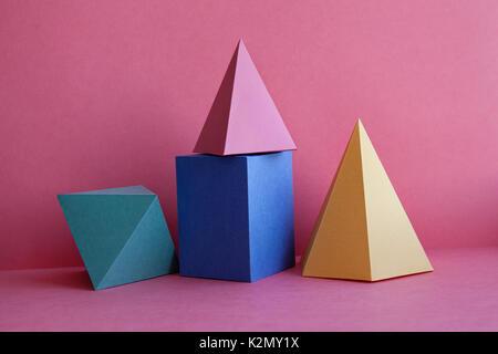 Solides platoniciens, composition géométrique abstraite de natures mortes. Cube rectangulaire prisme pyramide sur fond de papier rose. Couleur jaune bleu rose vert - image du fichier